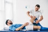 Fyzioterapeutka masáž nohou fotbalového hráče na masážním stole v nemocnici