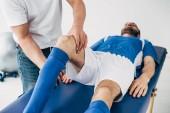 Fyzioterapeutka masáž nohou fotbalového hráče v nemocnici