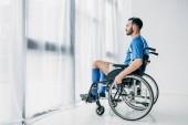 Mann in Fußballuniform sitzt im Rollstuhl und schaut durch Fenster