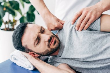 selective focus of chiropractor massaging shoulder of man in hospital