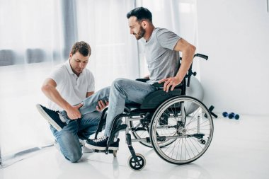 Physiotherapist massaging leg of handicapped man in wheelchair