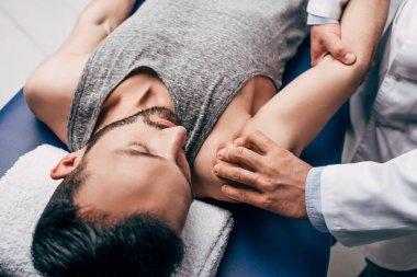 chiropractor massaging shoulder of man on Massage Table in hospital