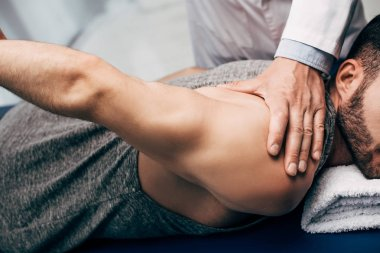 Physiotherapist stretching arm of patient in hospital