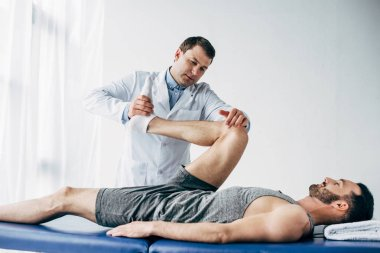 handsome chiropractor stretching leg of patient in hospital