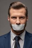 stattliche Geschäftsmann im Anzug mit Klebeband auf Mund isoliert auf grau