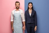 Fotografie smiling man in apron and businesswoman holding hands on blue and pink