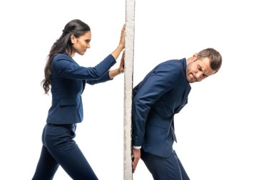 businessman and businesswoman in suits pushing wall isolated on white