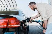 Bärtiger Mann hält Zapfsäule und tankt schwarzes Auto an Tankstelle