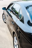 selective focus of shiny black and modern car in parking