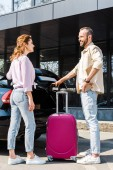 handsome and cheerful man looking at happy woman while standing near car and pink luggage