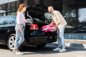 low angle view of happy man putting pink luggage in car trunk near woman