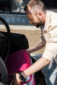 happy and bearded man smiling while putting pink luggage in car trunk