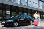 happy man hugging cheerful woman while standing near black car with pink luggage