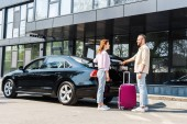 cheerful man looking at happy woman while standing near car and pink luggage