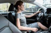 selective focus of attractive woman in glasses driving car