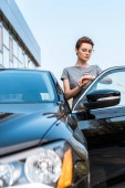 selective focus of woman in glasses looking at watch while standing near black car