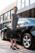 low angle view of attractive businesswoman standing near black car with briefcase