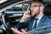 selective focus of angry bearded businessman talking on smartphone and gesturing in car