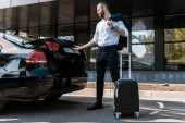 low angle view of happy businessman opening car trunk while standing near luggage