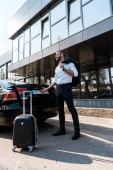 low angle view of happy businessman standing near black car with luggage