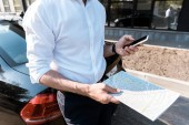 cropped view of businessman holding smartphone and map while standing near car