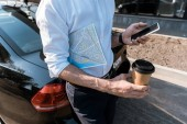 cropped view of man using smartphone while holding paper cup near car