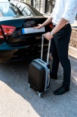 cropped view of businessman opening car trunk while standing with luggage