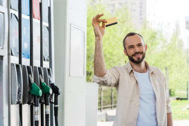 happy bearded man holding credit card and smiling at gas station