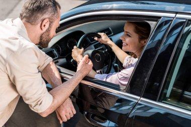 overhead view of man standing near happy woman holding steering wheel in car