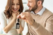 selective focus of handsome man holding car key and looking at happy brunette woman