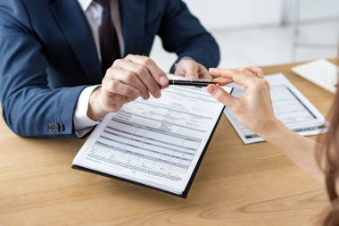Cropped view of car dealer giving pen to woman while holding clipboard with document stock vector