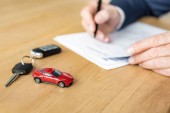 selective focus of red toy car near car key and car dealer holding pen near contract