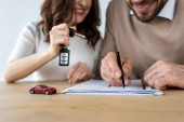 selective focus of red toy car near bearded man signing contract and woman holding car key