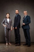 low angle view of businesswoman standing with hand on hip near handsome businessmen on grey