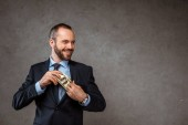 happy businessman putting dollar banknotes in pocket on grey