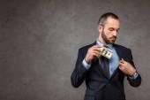 successful businessman putting dollar banknotes in pocket on grey