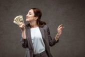 cheerful businesswoman with closed eyes smelling dollar banknotes on grey