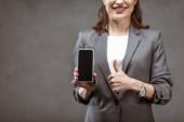 selektivní zaměření veselé ženy ukazující palec nahoru a přidržující smartphone s prázdnou obrazovkou na šedé