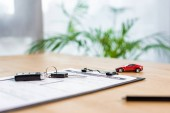 selective focus of  car key on clipboard with document near pen and toy car