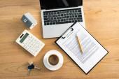 pohled na šálek kávy v blízkosti notebooku a schránky se smlouvou o pronájmu na stole