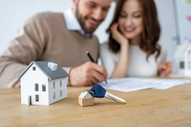 selective focus of house model and keys near happy man and woman