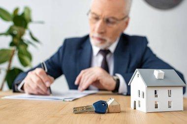selective focus of keys and house model near house dealer in glasses