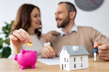 selective focus of happy woman putting golden coin in pink piggy bank near cheerful man