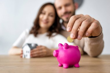 selective focus of man putting coin in pink piggy bank and cheerful woman