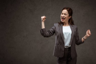 excited brunette woman celebrating triumph while standing on grey