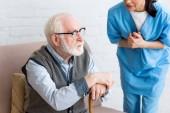 Vágott kilátás nővér beszél a szürke hajú férfi sétapálca