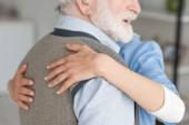 Fotografie Ausgeschnittene Ansicht der Krankenschwester, die mit grauhaarigem und lächelndem Mann umarmt