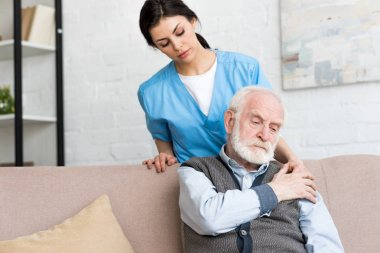 Doctor standing behind sad senior man, putting hand on his shoulder stock vector