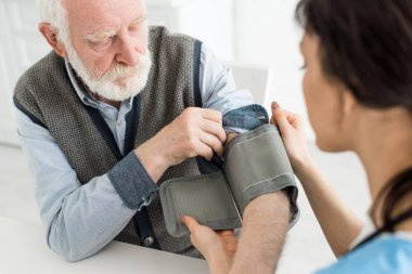 Selective focus of nurse measuring blood pressure of grey haired man