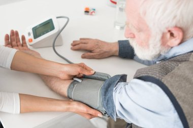 Cropped view of nurse measuring blood pressure of senior man
